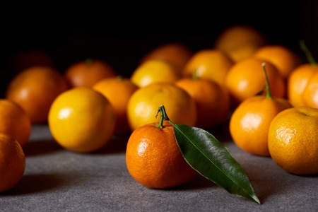 selective focus of orange clementine with green leaf near tangerines on grey table