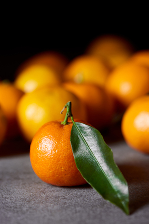 selective focus of sweet clementine near tangerines with green leaf