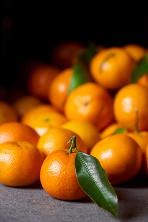 selective focus of sweet orange tangerine near clementines with green leaves Stock Photo
