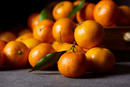 selective focus of tasty orange tangerines with green leaves Stock Photo