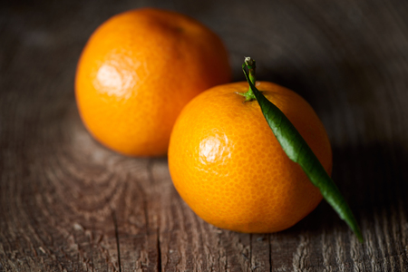 selective focus of juicy orange tangerines on wooden table
