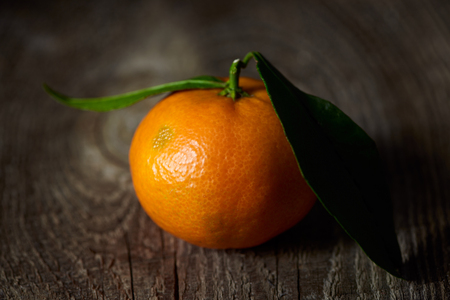 selective focus of organic tangerine with green leaves on wooden table 版權商用圖片
