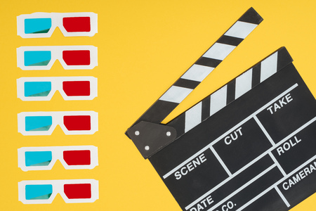 3d glasses in vertical row and clapperboard isolated on yellow