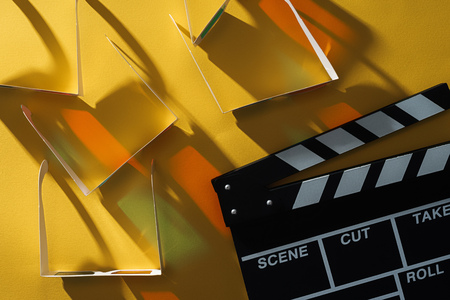 top view of 3d glasses with shadows and clapperboard on yellow background