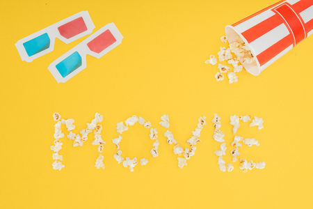 3d glasses, overturned striped bucket and movie lettering made with popcorn  isolated on yellow Stock Photo