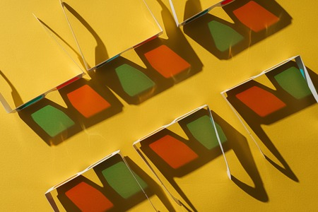top view of cardboard 3d glasses in two rows with shadows on yellow background Stock Photo