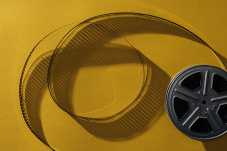 top view of movie reel with twisted cinema tape on yellow background Imagens