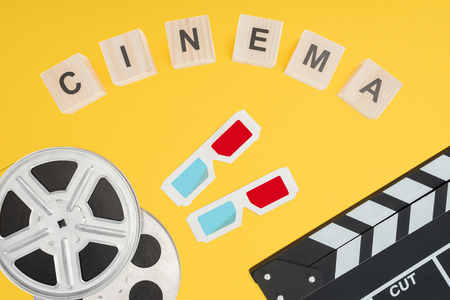 cubes with cinema lettering, 3d glasses, clapperboard and film reels isolated on yellow Stock Photo