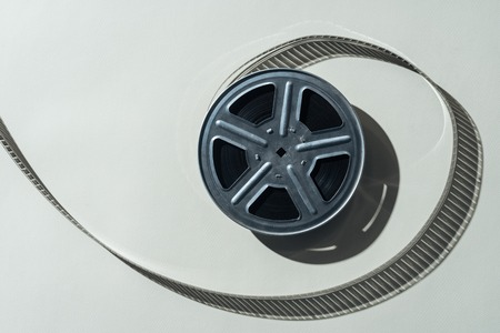 top view of film reel with twisted cinema tape on grey background