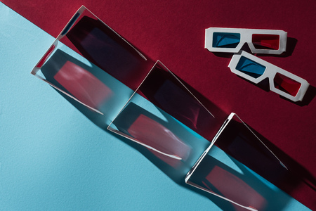 top view of 3d glasses with shadows on blue and bordo background