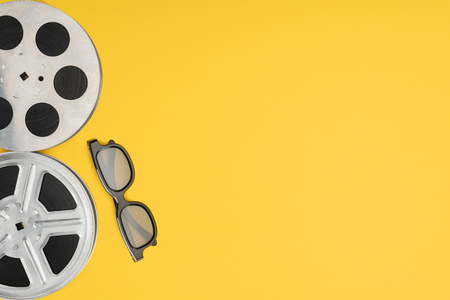 film reels and stereoscopic 3d glasses isolated on yellow