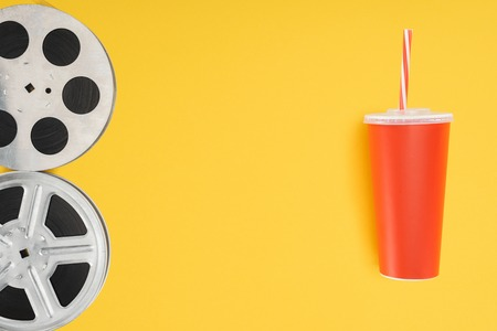 film reels and red disposable cup with straw isolated on yellow Фото со стока
