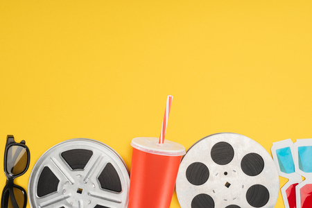 3d glasses, film reels and red disposable cup with straw isolated on yellow Stock Photo