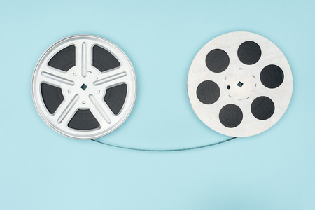 film reels with cinema tape between them isolated on blue