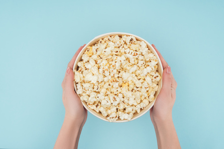 top view of hands holding bucket with popcorn isolated on blue