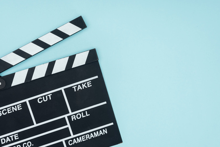 opened black movie clapperboard isolated on blue Banco de Imagens