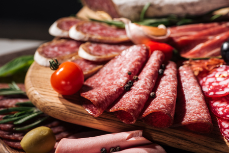 close up view of wooden cutting board with delicious sliced salami and vegetables Imagens