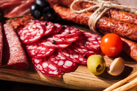 close up view of wooden cutting boards with delicious smoked sausages, vegetables and sliced salami
