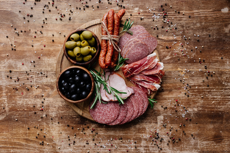 top view of round cutting board with delicious salami, prosciutto and olives in two bowls on wooden table with scattered spices