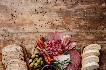 top view of cutting boards with delicious bread, salami, smoked sausages, ham and olives on wooden table with scattered peppercorns
