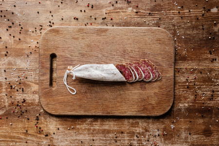 top view of cutting board with delicious sliced salami on wooden table with scattered peppercorns Reklamní fotografie