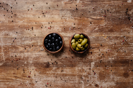 top view of two bowls with black and green olives on wooden table with scattered peppercorns 版權商用圖片