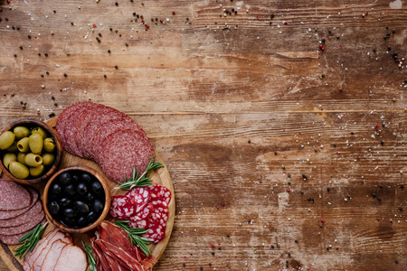 top view of cutting board with olives, breadsticks, delicious prosciutto, salami and herbs on wooden table with scattered spices Archivio Fotografico