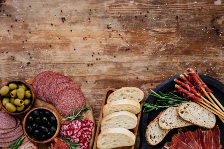 top view of cutting boards with olives, breadsticks, prosciutto, salami, bread and herbs on wooden vintage table