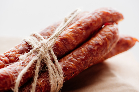 close up view of smoked sausages tied with string on brown wrapping paper
