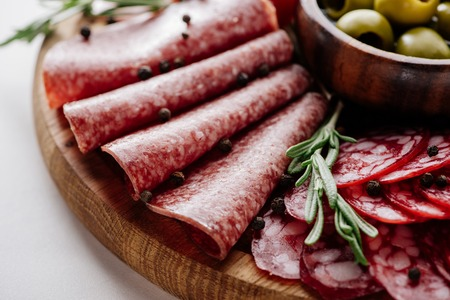 close up view of delicious sliced salami with rosemary and peppercorns on wooden cutting board