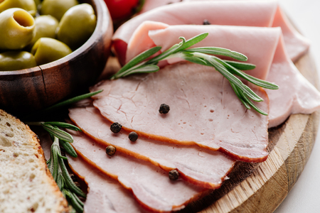 close up view of olives in bowl and delicious sliced ham with spices and herbs on wooden cutting board 版權商用圖片