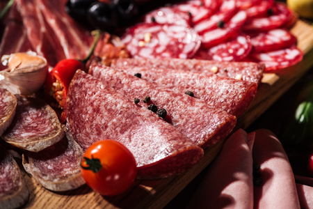 close up view of sliced salami with tomato, peppercorns and chili on wooden cutting board