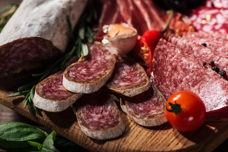 close up view of sliced salami with vegetables on wooden cutting board Imagens