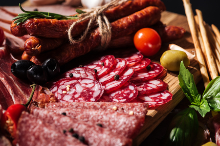 close up view of delicious smoked sausages and sliced salami with vegetables on wooden cutting board