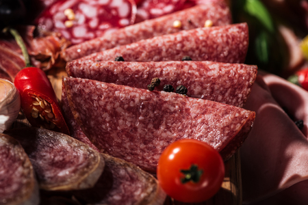 close up view of tasty sliced salami with vegetables and spices on wooden cutting board