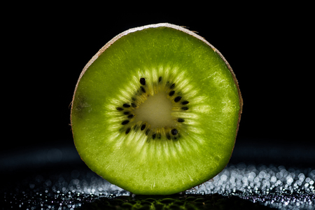 slice of fresh kiwi fruit on black background Stock Photo