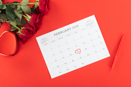 top view of roses and calendar with 14th february date marked with heart isolated on red, st valentines day concept