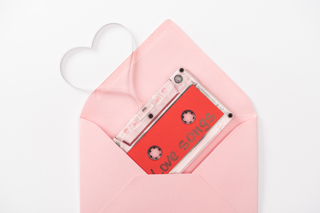 top view of audio cassette with love songs lettering and heart symbol in envelope isolated on white, st valentines day concept