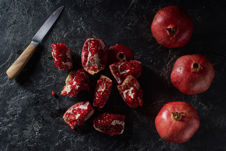 Top view of ripe pomegranates and knife on textured surface