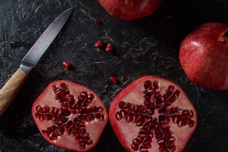 Top view of cut pomegranates with knife Stock Photo