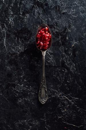 Top view of vintage spoon with garnet seeds 版權商用圖片
