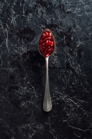 Top view of spoon with pomegranate seeds on dark surface