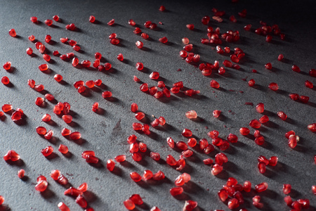 Studio shot of garnet seeds on dark surface