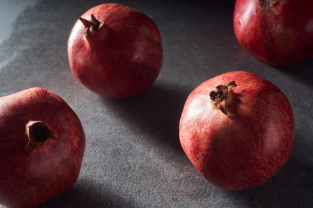 Studio shot of fresh pomegranates on black surface