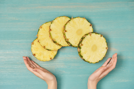 cropped view of female hands near sliced circles of pineapple on turquoise wooden table 版權商用圖片