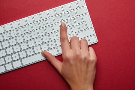 Top view of woman pushing button on white computer keyboard on red background