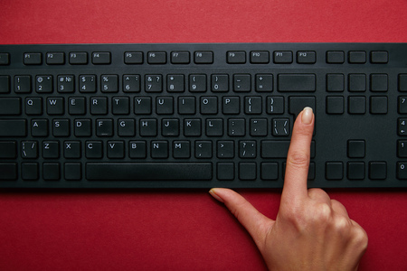 Top view of woman pushing button on black computer keyboard on red background