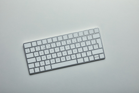 Top view of white computer keyboard on grey background