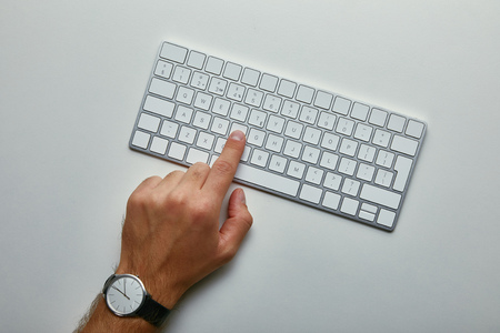 Cropped view of man pushing button on computer keyboard on grey background 스톡 콘텐츠