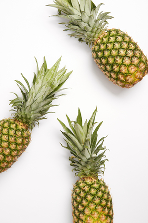top view of tasty organic pineapples on white background